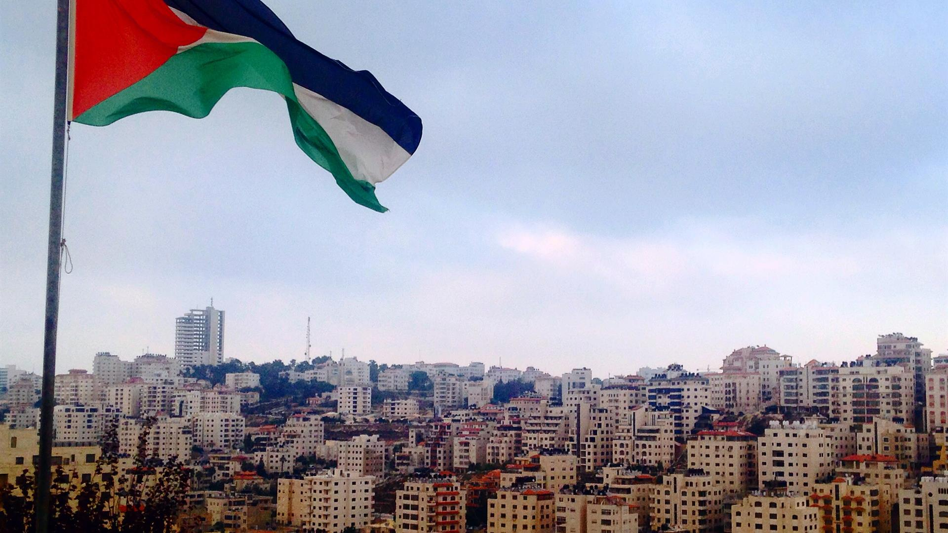 Palestine Flag Fluttering In The Sky Of The City Of Ramallah